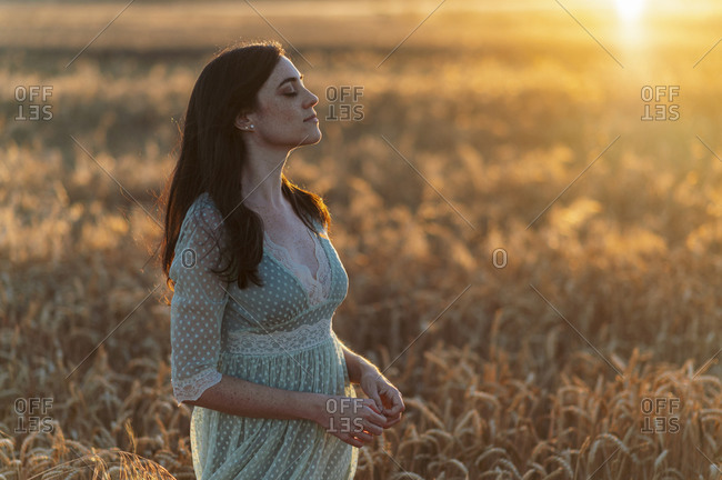 Young woman with eyes closed standing amidst wheat crops in farm at sunset