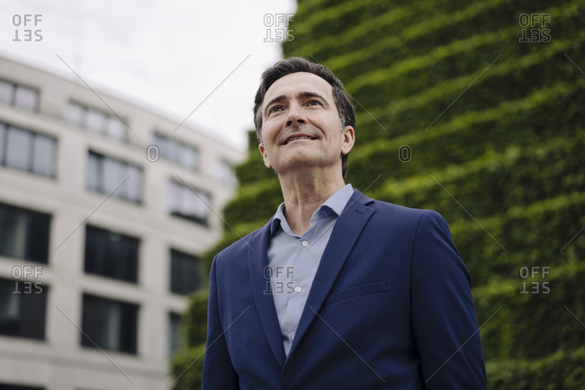 Portrait of a smiling mature businessman in the city looking up