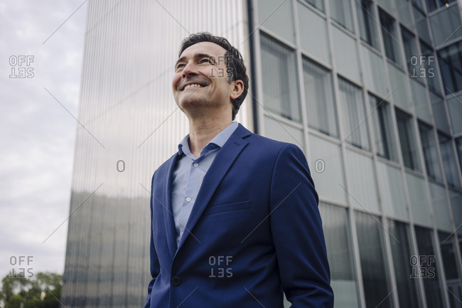 Happy mature businessman in the city looking up