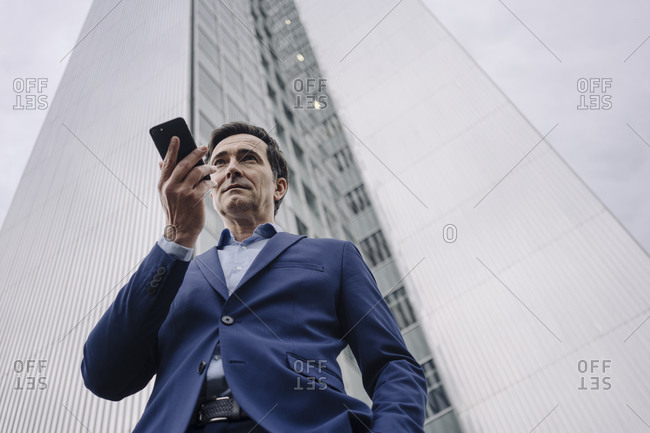 Mature businessman with smartphone in front of an office tower in the city
