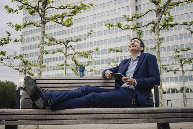 Happy mature businessman sitting on a bench in the city with moka pot and tablet