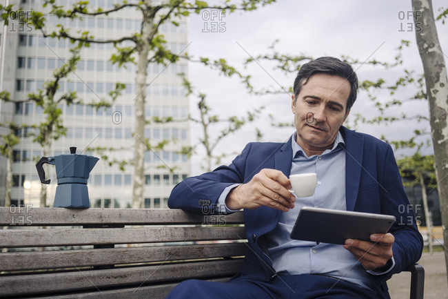 Mature businessman sitting on a bench in the city with espresso and tablet