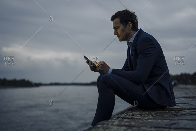 Mature businessman using tablet at the riverbank at dusk