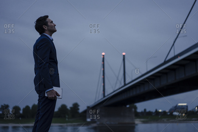 Mature businessman holding tablet standing at the riverbank at dusk