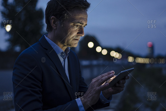 Mature businessman using tablet on a promenade at dusk