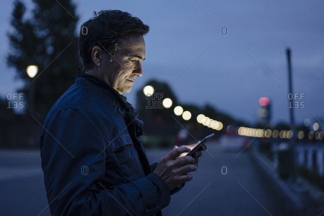Mature man using tablet on a promenade at dusk