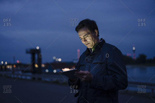Mature man using tablet at the riverbank at dusk