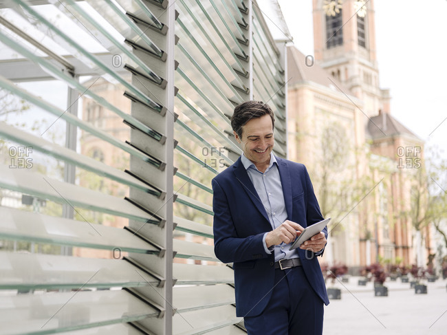 Smiling mature businessman using tablet in the city