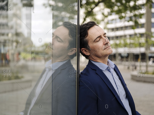 Exhausted mature businessman leaning against glass wall in the city