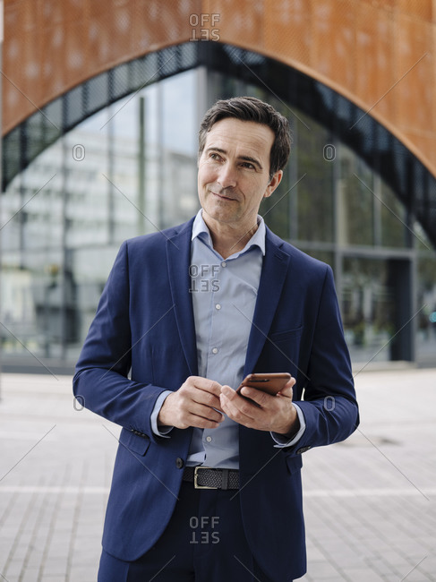 Mature businessman with smartphone in the city looking around