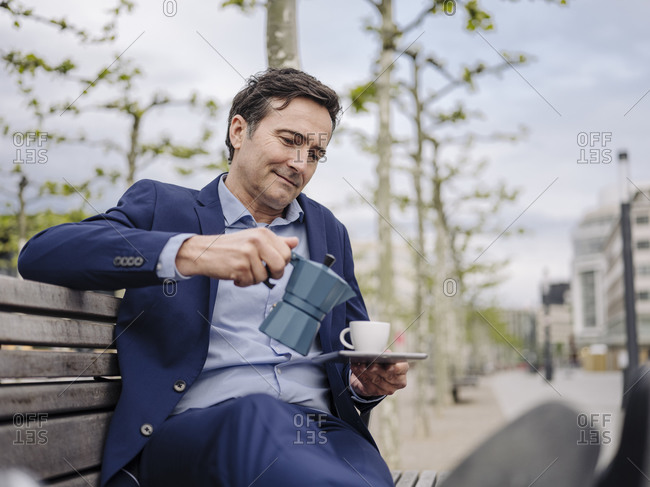 Mature businessman sitting on a bench in the city pouring espresso into cup