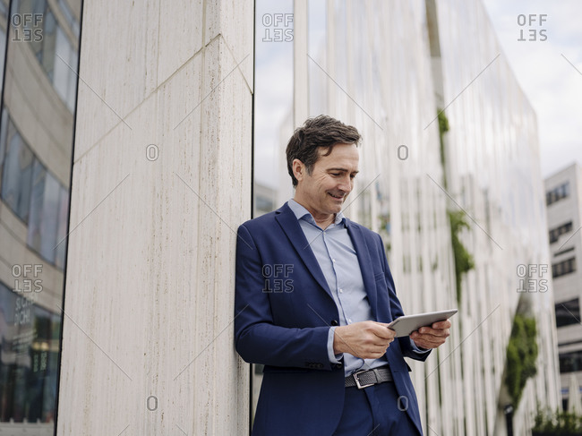 Mature businessman leaning against a building in the city using tablet