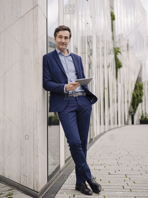 Mature businessman with tablet leaning against a building in the city