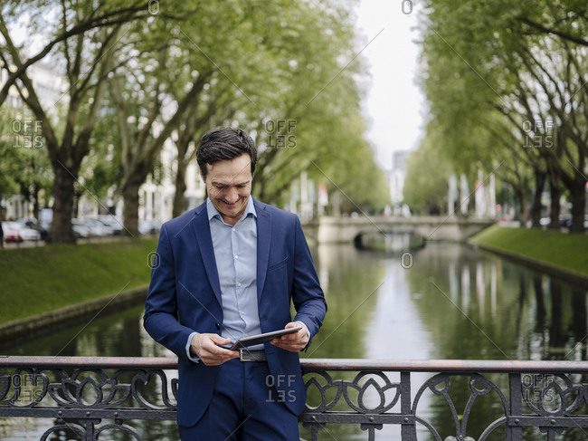 Mature businessman standing on a bridge using tablet