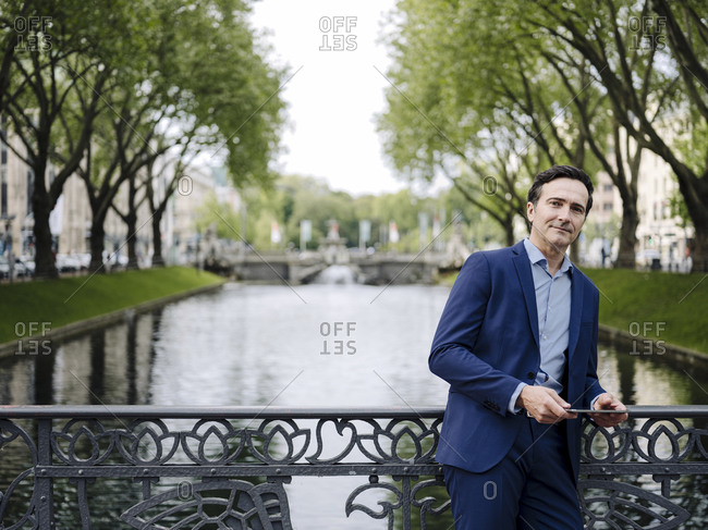 Portrait of a confident mature businessman standing on a bridge with tablet