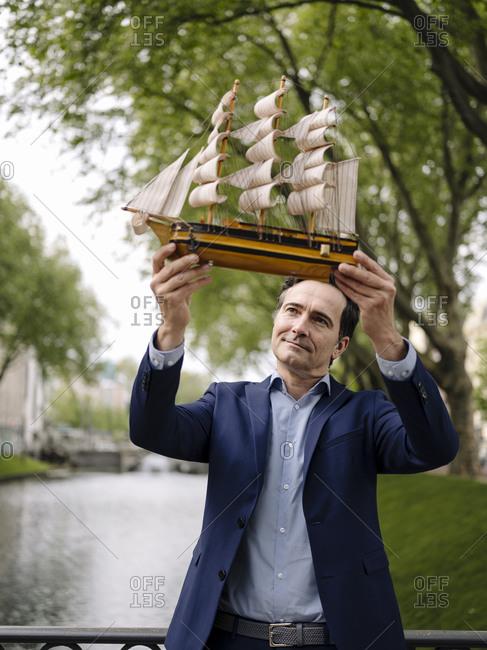 Mature businessman holding model sailing ship on a bridge