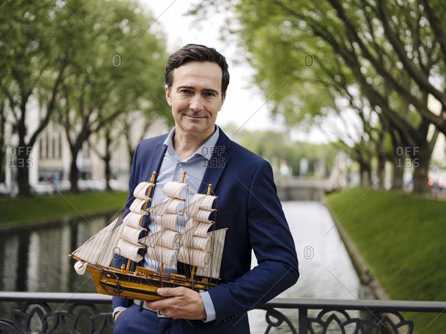 Portrait of a confident mature businessman holding model sailing ship on a bridge