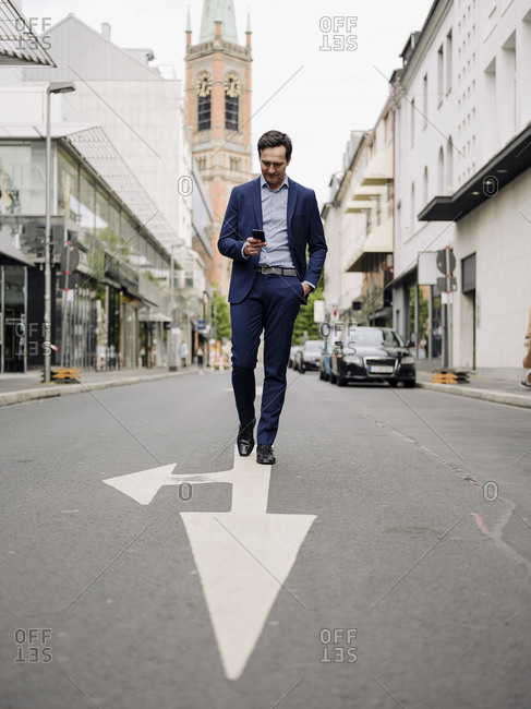 Mature businessman walking on a city street using smartphone