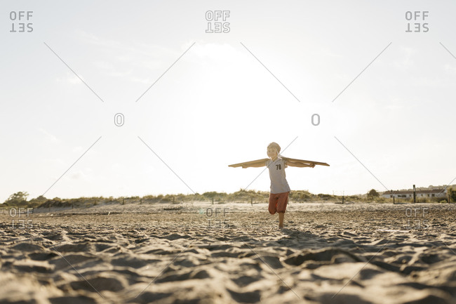 Boy running with cardboard wings at beach during summer