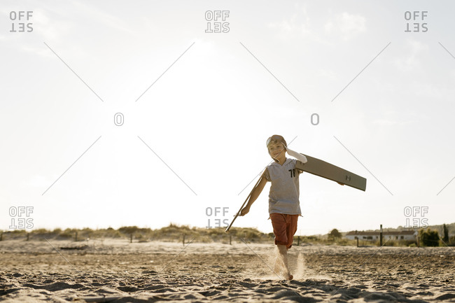 Boy wearing aviator's cap while running with cardboard wings on beach