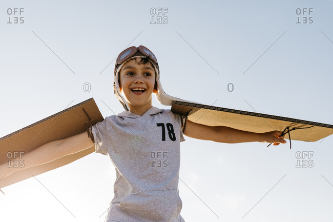 Boy wearing aviator's cap and cardboard wings against sky