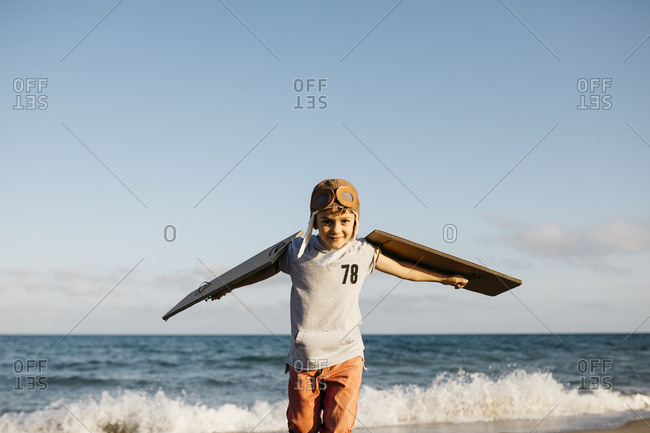 Boy wearing aviator's cap and cardboard wings at beach
