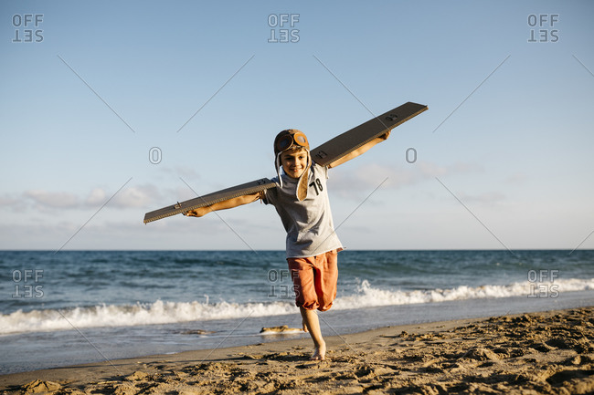 Boy running with cardboard wings and aviator's cap at beach