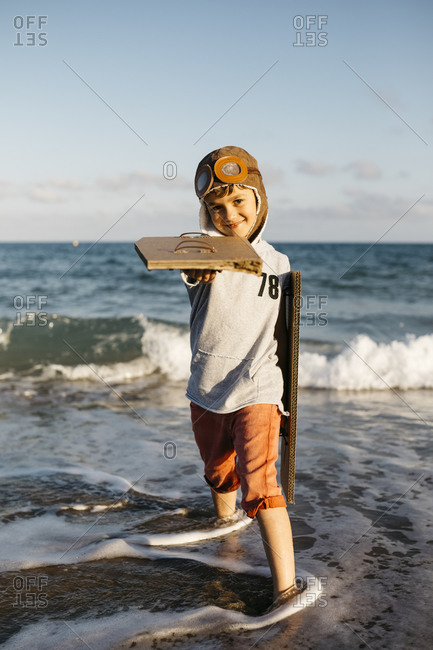 Boy with aviator's cap holding cardboard wings while standing at beach