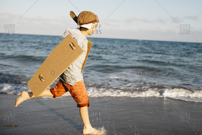 Boy with aviator's cap and cardboard wings running at beach