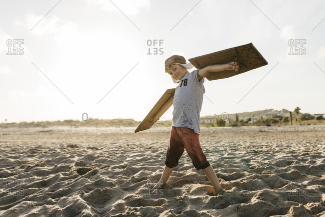 Boy wearing aircraft wings and cap while standing with arms outstretched at beach