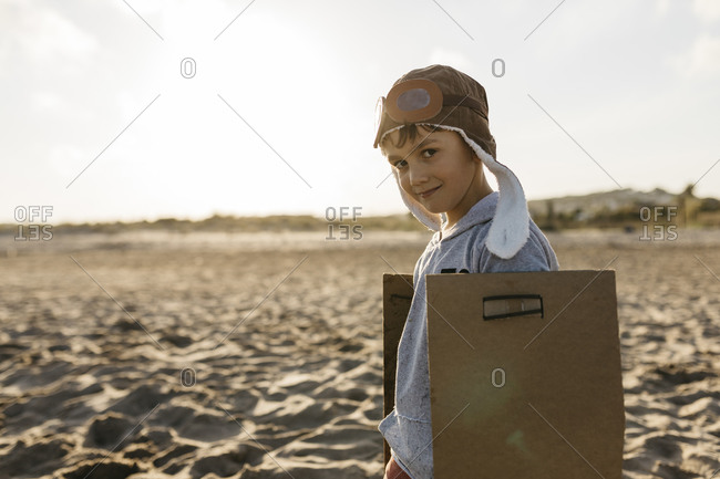 Smiling boy with aircraft wings and cap standing at beach