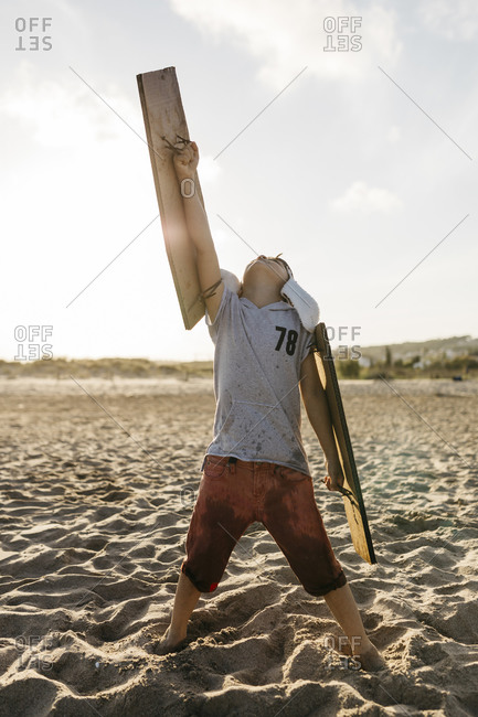 Boy wearing aircraft wings and cap standing with arm raised at beach