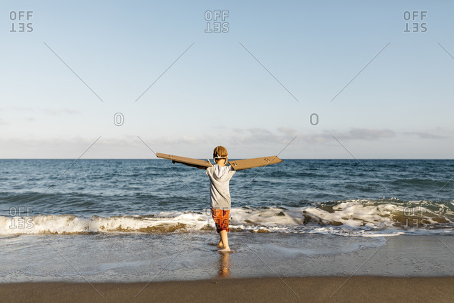 Boy wearing aircraft wings while standing with arms outstretched at beach