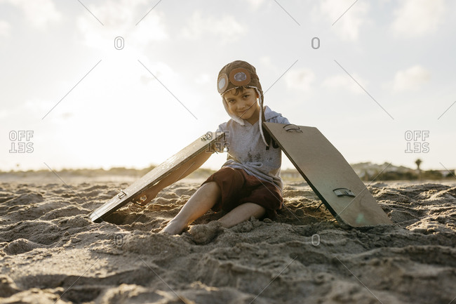 Boy with aircraft wings and cap sitting on sand at beach