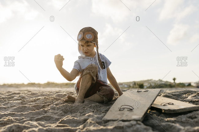 Boy wearing aviator's cap showing muscle while sitting on beach