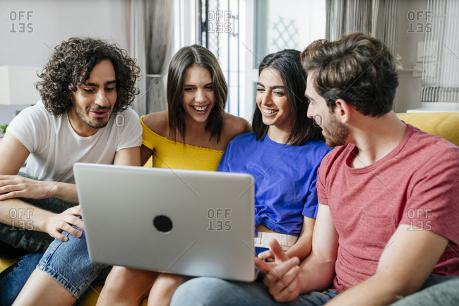 Smiling multi-ethnic friends sharing laptop while sitting in living room