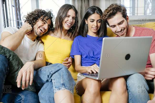 Happy multi-ethnic friends sharing laptop while sitting in living room
