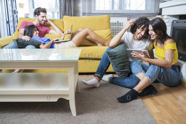 Happy young couples using technologies while sitting in living room