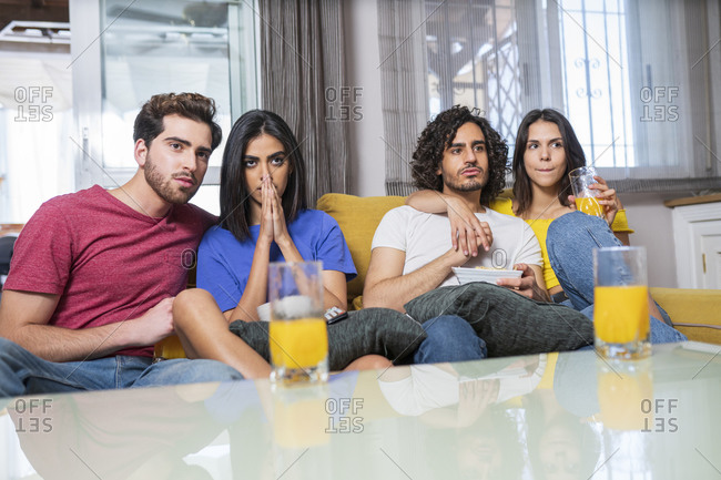 Young multi-ethnic friends in stress watching TV at home