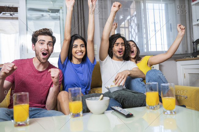 Cheerful young male and female fans cheering while watching TV at home