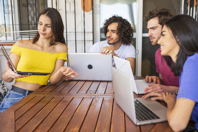 Young woman showing laptop to multi-ethnic friends sitting at table in back yard