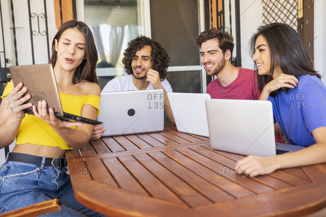 Young woman showing laptop to smiling multi-ethnic friends sitting at table in back yard