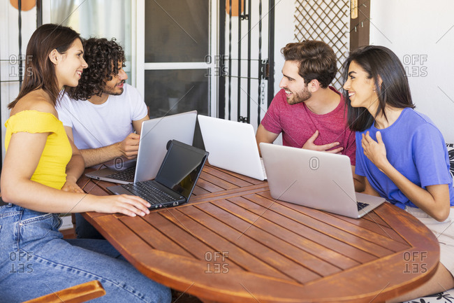 Happy young male and female friends talking while sitting with laptops at table in back yard