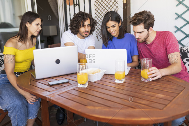 Young men and women sharing laptop while sitting at table in back yard