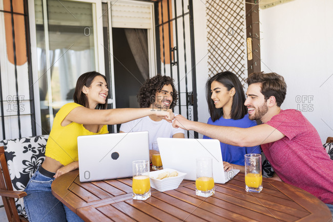 Smiling man and woman giving fist bump while sitting with friends at back yard
