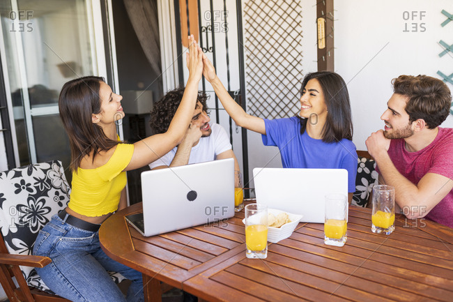Young women giving high-five while sitting with male friends at back yard