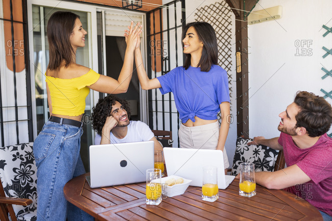Beautiful young women giving high-five by male friends at back yard