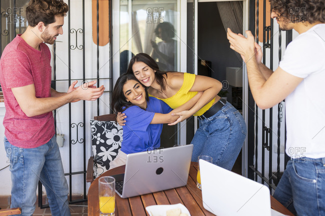 Young men clapping while looking at smiling beautiful women embracing at back yard