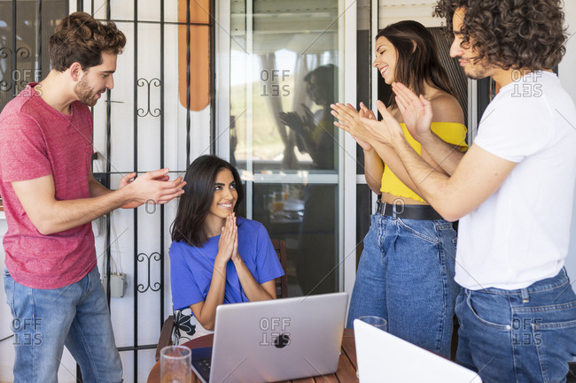 Happy friends applauding for beautiful young woman sitting with hands clasped at back yard
