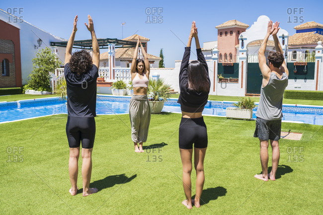 Young male and female friends learning yoga from woman at back yard on sunny day